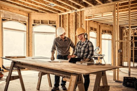 Construction workers discuss over a blueprint.