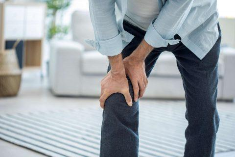 Man in pain holding upper leg