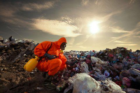 Man inspecting toxic waste dump