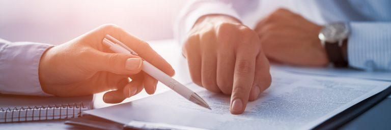 finger and pen pointing at paperwork.