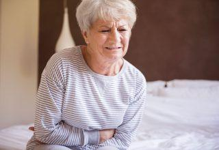 Elder woman holds her stomach in pain