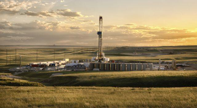 A lone drilling Fracking Rig set against the dramatic landscape of the American Prairie lands.  The sun is setting just off camera creating beautiful yellows and oranges on the clouds above.  In the far distance, wind turbines are visible.